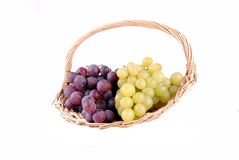 Red and green grapes in a straw basket Royalty Free Stock Photography