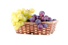 Red and green grapes in a straw basket Royalty Free Stock Photo