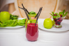 Red and green healthy smoothies with fresh ingredients on table. Stock Image