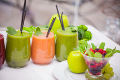 Red and green healthy smoothies with fresh ingredients on table. Royalty Free Stock Image