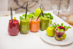 Red and green healthy smoothies with fresh ingredients on table. Stock Photo