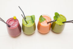Red and green healthy smoothies on table. Stock Photos
