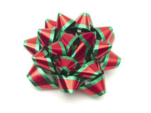 Red and green holiday gift ribbon. Shiny metallic red and green rosette ribbon for gift wrapping stock images