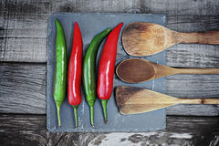 Red and green hot chili pepper on wooden background. royalty free stock image