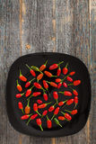 Red and green hot peppers on a black plate  old wooden boards. Red and green hot peppers on a black ceramic plate and old wooden boards Stock Photos