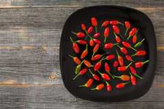 Red and green hot peppers on a black plate in style  rustic Stock Photo