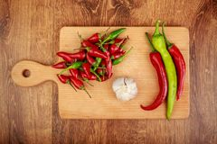 Red and green hot peppers and garlic on light brown wooden board on dark brown wooden table. Flat lay design Stock Photo