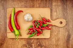 Red and green hot peppers and garlic on light brown wooden board on dark brown wooden table. Flat lay design Stock Photos