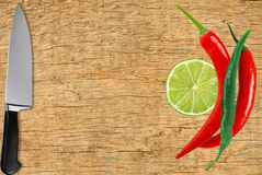 Red and green hot peppers, knife and lime slice on wooden table Royalty Free Stock Photo