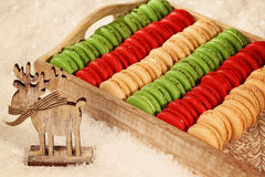 Red and green macaroons on wooden plate Royalty Free Stock Images