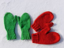 Red and green mittens. Two pairs hand knit mittens on fresh snow Stock Images