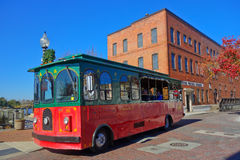 Red and green old trolley bus on Water Street. This free trolley bus goes around the city of Wilmington, North Carolina following points of interest like the big Stock Image