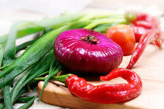 Red and green onions, red chilli peppers, closeup. Stock Images
