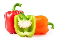 Red green orange bell peppers with half isolated on white Stock Photos