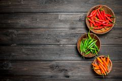 Red, green, orange pepper in bowl. On black wooden background royalty free stock photography