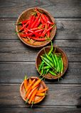 Red, green, orange pepper in bowl. On black wooden background stock images