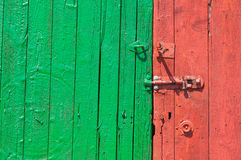 Red and green painted wooden door with bolt Royalty Free Stock Photos
