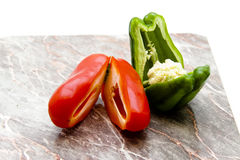 Red and green paprika. On edge board Stock Photography