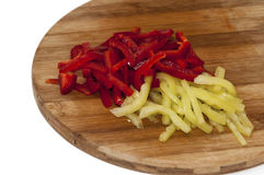 Red and green paprika sliced into strips on the wooden cutting board Stock Photo