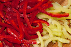 Red and green paprika sliced into strips on the wooden cutting board Stock Image