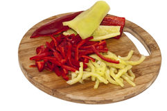 Red and green paprika sliced into strips on the wooden cutting board Stock Images