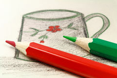 Red and green pencils on the background of a children`s drawing Royalty Free Stock Photos