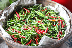 Red and green pepper in bamboo basket Stock Photos