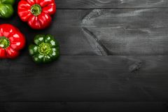 Red and green pepper on black wood background. Fresh vegetables. Top view stock photography
