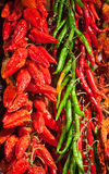Red and green pepper in bunches above counter Royalty Free Stock Photos