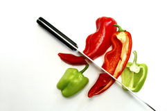 Red and green peppers. Isolated, artistic still life of a knife and two peppers, shot from above Royalty Free Stock Image
