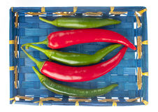 Red and green peppers in a blue basket. Stock Image