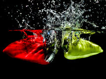 Red and green peppers making water splash Royalty Free Stock Image