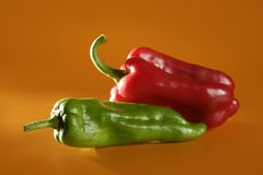 Red and green  peppers over orange  background Stock Photo