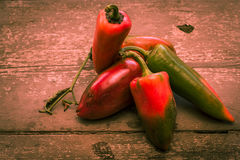 Red and green peppers on rough wooden table stock photography