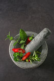 Red and green peppers in a stone dishware on a table Royalty Free Stock Image