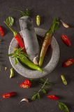 Red and green peppers in a stone dishware on a table Royalty Free Stock Images