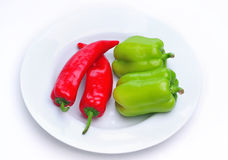 Red and Green peppers on a white plate. Red and Green peppers coupled together on a white plate with a white background Royalty Free Stock Image