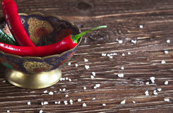 Red and green peppers on a wooden background Royalty Free Stock Images