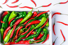 Red and green peppers in the wooden box stock photos