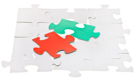 Red and green pieces on assembled white puzzles Stock Image