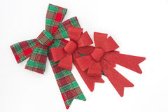Red and green plaid bow with two red holiday bows. Arranged on a white background Royalty Free Stock Image