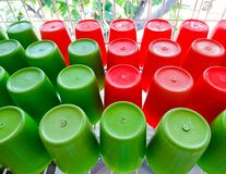 Red and green plastic cup. S were placed on the white shelf after cleaning stock image