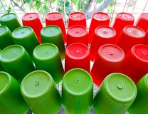 Red and green plastic cup. S were placed on the white shelf after cleaning stock photos