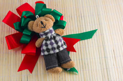 Red and green ribbon with bear doll on wood background. merry ch Stock Photo