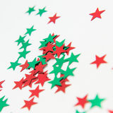 Red And Green Shiny Stars. Shiny red and green star embellishments close-up isolated on white background Royalty Free Stock Image