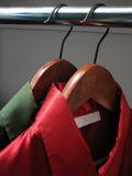Red and green shirts in a closet. Stylish green and red shirts with an empty label, on wooden hangers in a closet stock photos