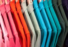 064ad8f9f95 Red green shirts on hang for sale in shop. Multicolored polo on wooden  hanger.