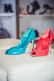 Red and green shoes lie on the storefront Royalty Free Stock Images