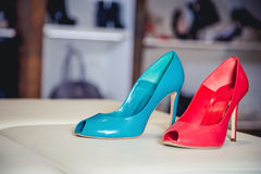 Red and green shoes lie on the storefront Stock Photography
