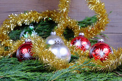 Red green and silver Christmas balls with silver stars. Around them christmas chain in gold color on old wooden table with green needles Stock Photo